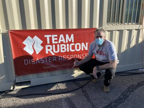 Dr. James Wiseman in front of a Team Rubicon Disaster Response banner